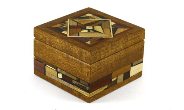 Small wooden box decorated with wood mosaics. No stains or dyes.Small wooden box decorated with multi wood mosaics on top and sides. No stains or dyes, just the natural colors of each wood.